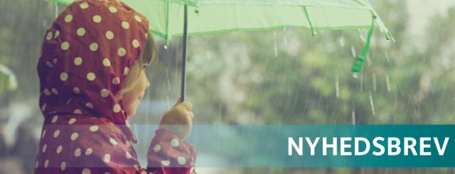 Pige i rød regnjakke står under paraply i regnvejr