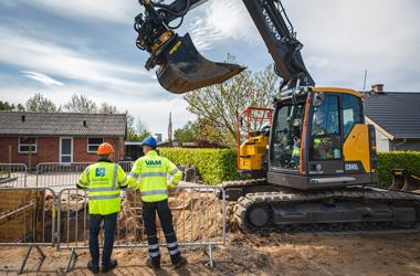 To mænd med arbejdstøj og hjelm kigger på gravemaskine, der graver i vejen