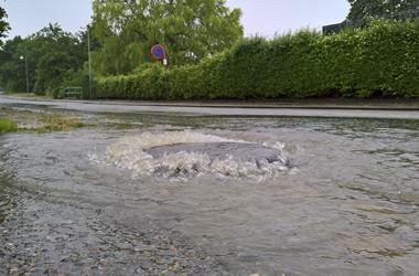 Vand strømmer ud af kloakdæksel i vej
