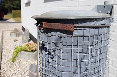 Affaldsstativ med grå affaldssæk står op ad hvid hus mur